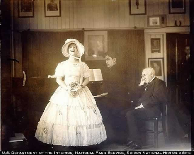 Dressed in an antebellum hoop dress and bonnet, Miss Davis delivers a song, as her patron, Edison, sits with a hand cupped to his ear, as if hard of hearing. Victor Young is accompanying her on the piano.