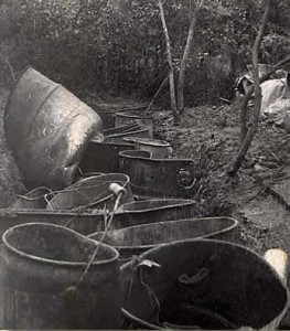 Photo: moonshine still. Filthy, battered tubs, barrels and buckets scattered about at the wooded moonshine-making site.