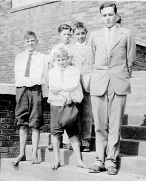 School boys, in knickers, white shirts and ties, and their teachers on church steps.