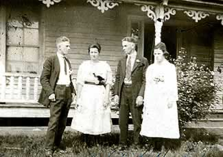 Two young married couples, in the front yard of the old house.