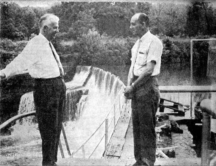 Paul Bridges and James Goode talk with the waterfall of Cliffside dam behind them.