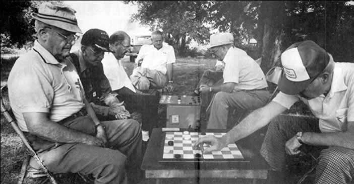 Two checker games in progress under a shade tree. Four players and three onlookers. All are old friends who frequently play together.