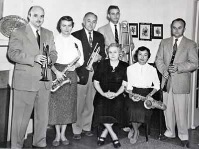Seven members of the Cole family each holding a musical instrument.