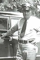 The stern-faced lawman in uniform stands beside his car.