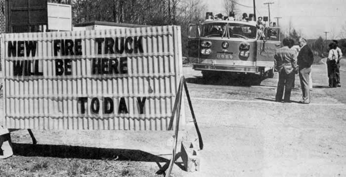 """A small clump of people admire the truck, parked along side the highway. The big sign in the foreground reads """"New fire truck will be here today."""""""