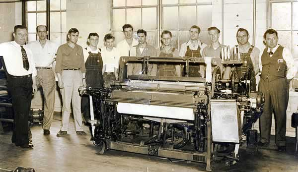 An actual loom is installed on the training floor, around which the fixers are grouped.