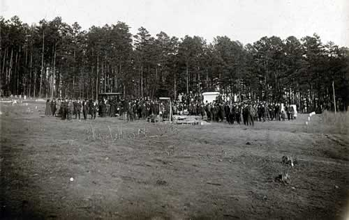 A long shot of the cemetery. It is the same funeral, and many more people are visible than in the previous photo.