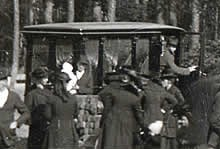Another closeup reveals a motorized hearse, not horse drawn