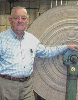 Herman Jones in the mill, standing by an enormous roll of denim cloth.