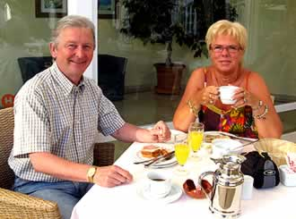 The handsome, middle-aged couple at breakfast in their charming home.