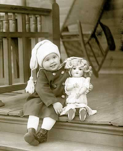 Little girl on steps with her dolly.