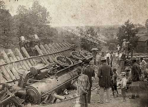 The huge locomotive engine lies on its side as onlookers marvel at the sight.