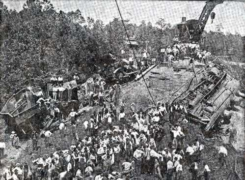 Another view of the devastation, revealing many mangled cars derailed and hundreds of workers surveying the carnage. A huge railroad crane looms over the scene.