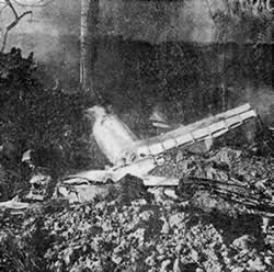 The remains of the fuselage, tail and one wing amidst rubble.
