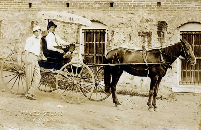 A one-seater buggy with a sunshade over the driver, in white shirt and tie, holding the reins as they sit still beside a brick wall of some building. Another man, on the ground, is standing beside the rig. He too is wearing a white shirt and tie. Both wear casual hats.