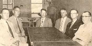 A half-dozen men sitting around a table.