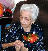 A pert lady with beautiful white hair, wearing her birthday corsage.