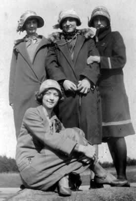Young girls in coats and cloche hat  having fun on a winters day.