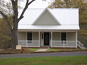 """White house on Main Street, in the """"old mill house"""" design."""