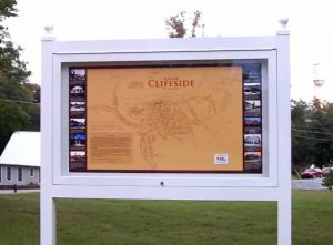 A large architectural map of Cliffside circa 1942 enclosed in a glass case on the grounds of the clock tower.
