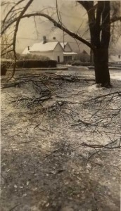 In the foreground small twigs and fallen ice clutter the ground on this gloomy day in Cliffside. Across the street is a large, white, snowy-roofed house, home of the Baptist preacher.