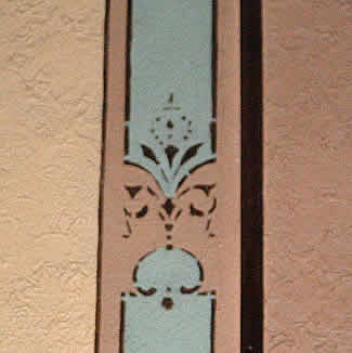 A stucco side wall with ornamental designs.