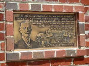 """A bronze plaque, about 14 inches wide by 7 inches embedded in the brick wall of the clock tower. It has a embossed face of Mr. Haynes and of his home. It reads """"In 1902 Raleigh Rutherford Haynes, one of the South's leading textile pioneers, and the founder of Cliffside, built his home on this site. After Haynes' death on February 6, 1917, his son Charles lived here for the next 40 years. The house was demolished in the 1970s. The Cliffside Historical Society."""""""