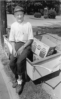 Sam, sleeves rolled up, sits in the summer heat on his rolling cart at curbside.