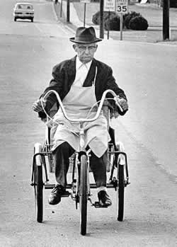 Sam, in hat and suit coat, no tie, his white shirt buttoned all the way up, wearing an apron, pedals his three-wheeled cycle down a Spindale street.