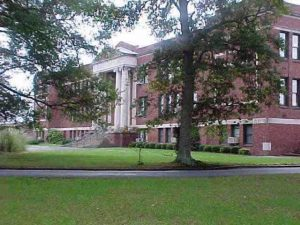 A beautiful color photo of the school with the green front lawn in the foreground