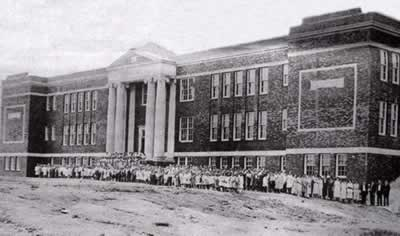 The new school with dozens of children and adults lined up across front.