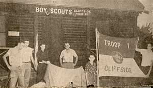 Front exterior of Scout Cabin. Boys holding troop guidon and artifacts.