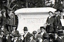 A close up of people standing on and around R. R. Haynes' large tombstone.