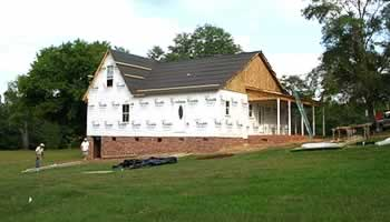Workmen behind house. Sheathing and Tyvek insulating wrap have been applied.