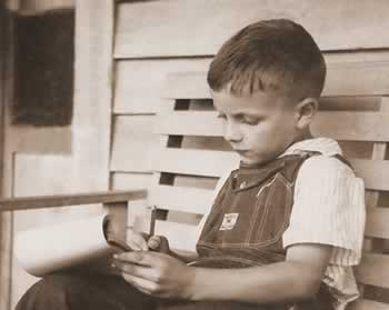 Age 6 or 7, writing in his Blue Horse tablet.