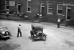 An overview of the main street in downtown Cliffside in 1937, with a Model A rounding the curve.  On the steps and loading dock of the hardware building, workers sit and wait.