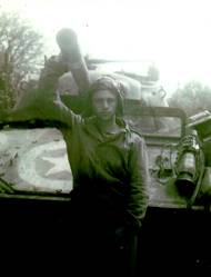 A helmeted James in front of his tank, reaching over his head grasping the long barrel of the tank's cannon.