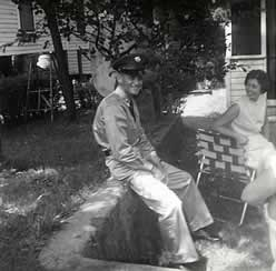 Front yard. Family sitting in lawn chairs. Buddy, in army uniform, sits on rock wall