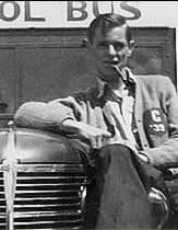 Glen sitting on the hood of a school bus.