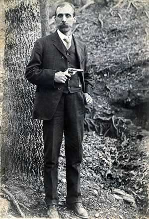 Haynes, mustachioed and well dressed in suit and tie, stands in a woodsy area. He is brandishing a revolver.