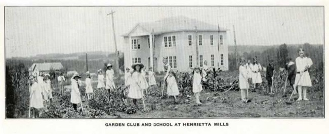 The small, two-story school stands in a tree-less landscape. A number of mostly young female students are hoeing around the plants in the garden.