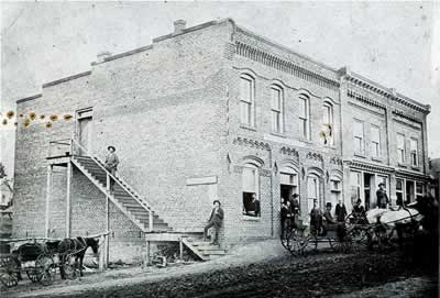 Photo circa 1900. Several men and mule-drawn wagons in front of building.