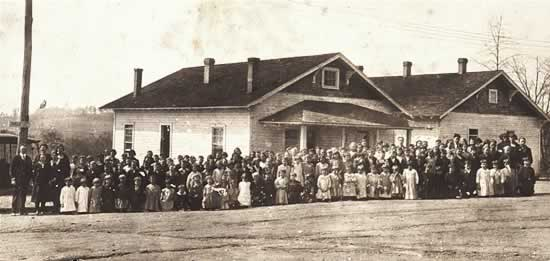 Sixty or seventy line up in the street in front of the wooden school, which is built in the same style as mill houses.