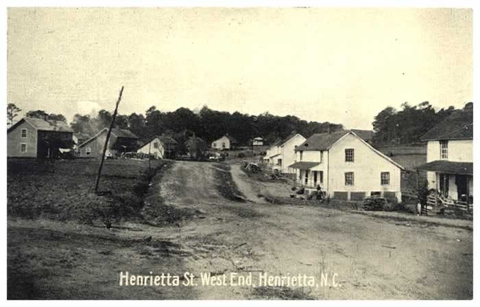 "Looking out Henrietta Street, a wide dirt throughfare. The caption locates it in ""West End, Henrietta, N. C."" West Henrietta."