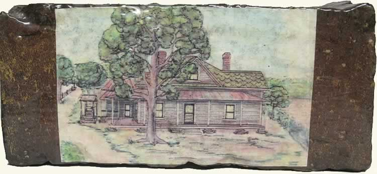 An old brick with a color drawing of the old house embedded on the brick's side.