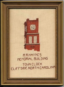 Photo of framed, completed cross stitch containing a likeness of a portion of the old clock tower, and the words 'R. R. Haynes Memorial Building. Town Clock, Cliffside, North Carolina.
