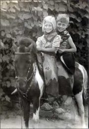 A little boy and girl in cowboy dress astride a pinto pony.