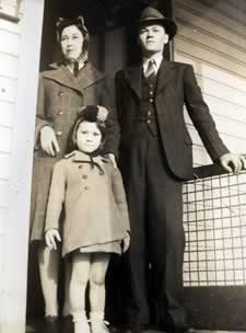 Family, dressed for church, standing in doorway to their home.