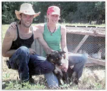 Young couple, dressed for farm work, with their dog, kneeling by a chicken coop.