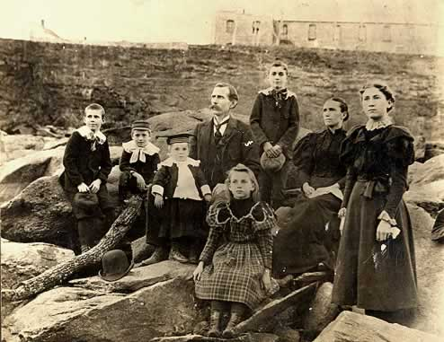 Family of eight posing on huge river rocks below the mill building.